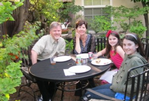 Photo of the four family members at a friend's house at a table.